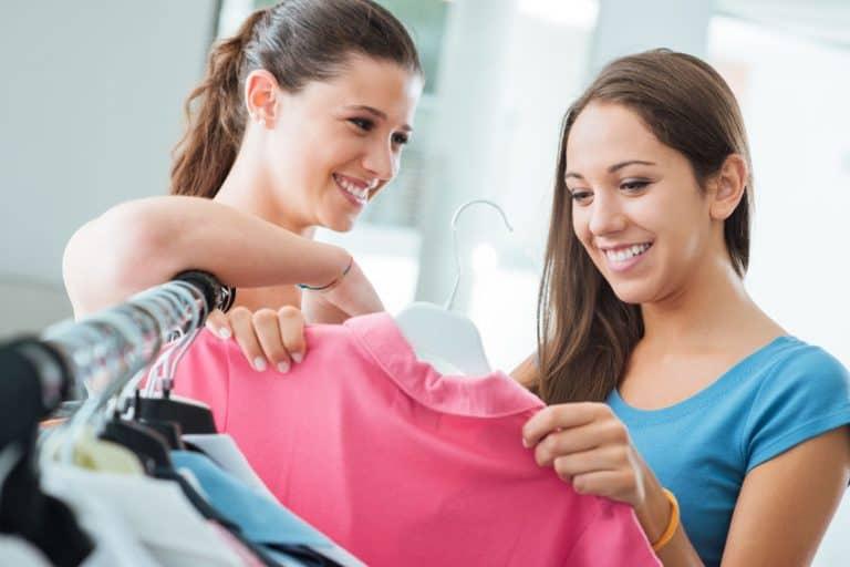 Imagem de duas mulheres mexendo em cabides de roupas.