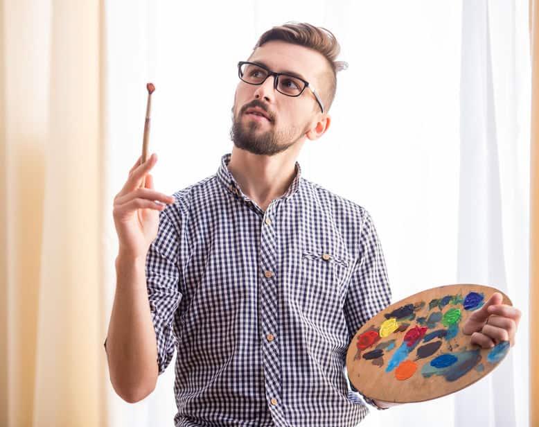 Imagem de homem segurando tinta e pincel aquarela.