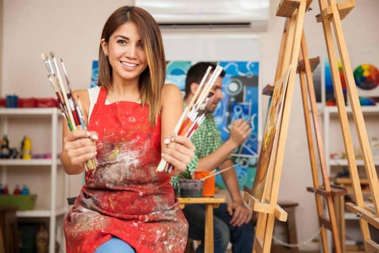 Imagem de mulher segurando pincéis.