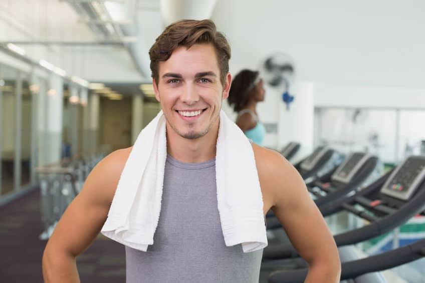 Homem com toalha em volta de pescoço em academia.