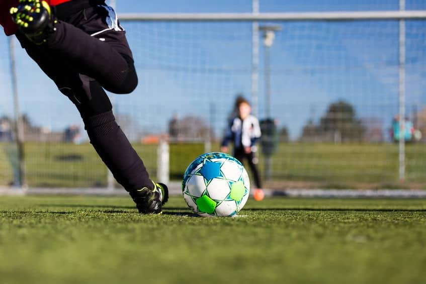 Jogo de futebol, pessoa chutando em direção a trave.