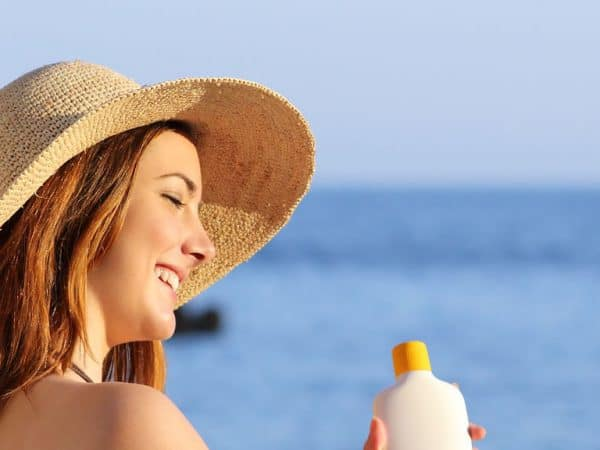 Woman on holidays  on the beach applying sunscreen protection on leg with the horizon in the background