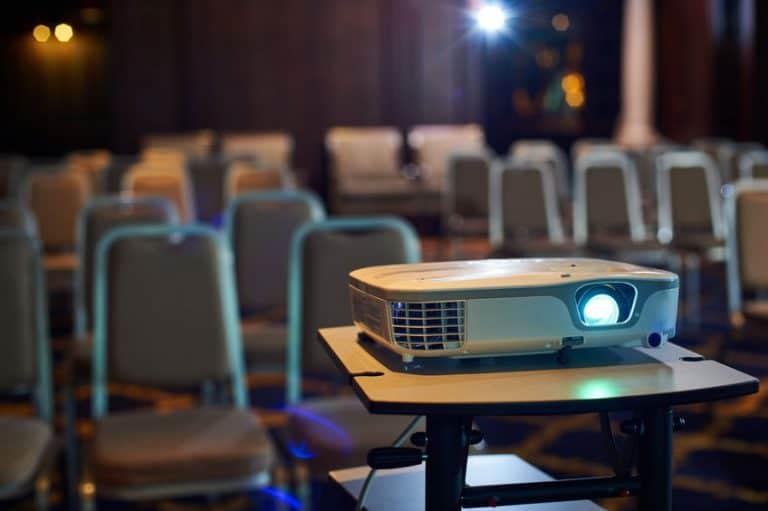 Uma sala vazia, cadeiras e um projetor sobre uma mesa