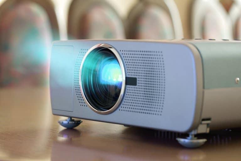 Imagem destaca um projetor sobre a mesa e luzes saindo através da lente