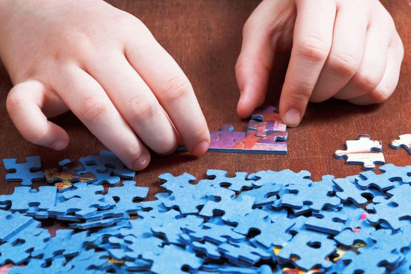 Imagem de criança montando peças quebra cabeça.