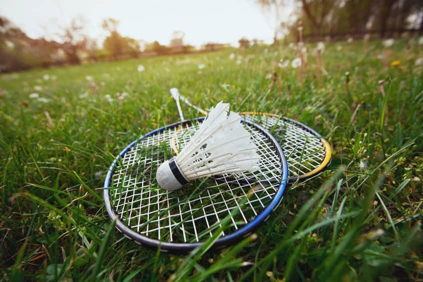 Imagem de raquetes de badminton em gramado.