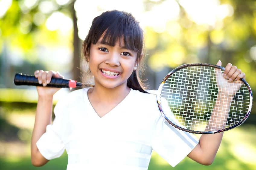Menina segurando raquete de badminton.