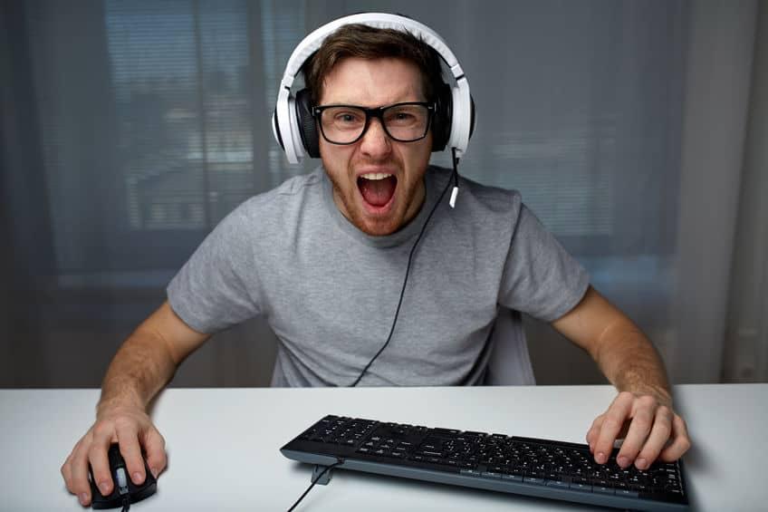 homem de fone com as mãos em um mouse e teclado gritando