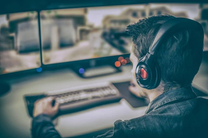 gamer com fone em frente a um computador