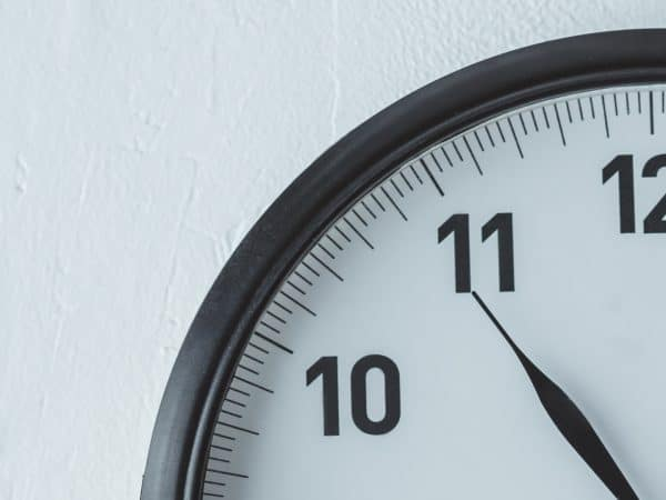 black clock on white wall with copy space