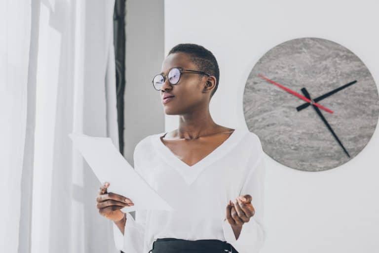 Imagem de mulher em sala com relógio ao fundo.