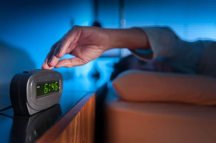 Imagem de pessoa desligando despertador.