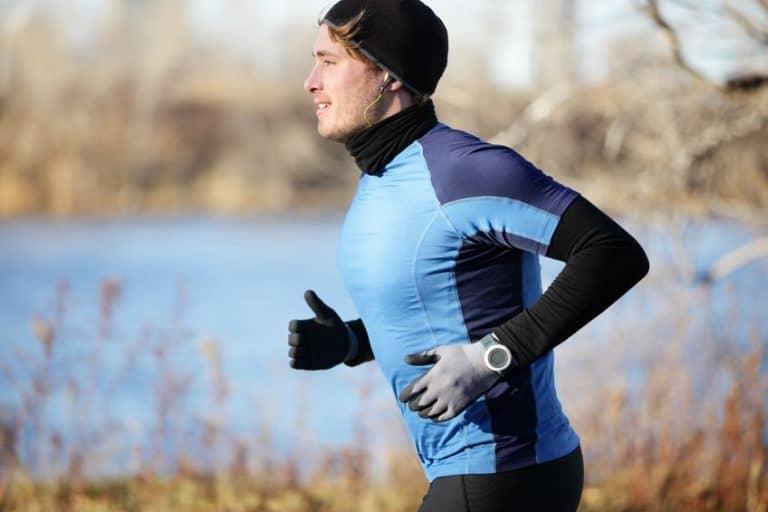 Homem correndo com relógio de pulso e fones de ouvido.