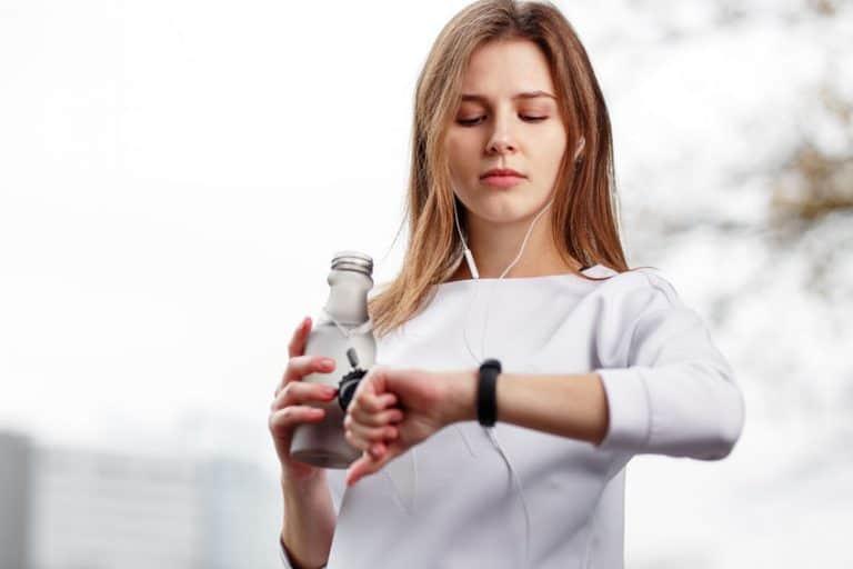Mulher segurando garrafa de água e olhando para o relógio.