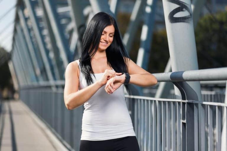 Imagem de mulher correndo, olhando para relógio.
