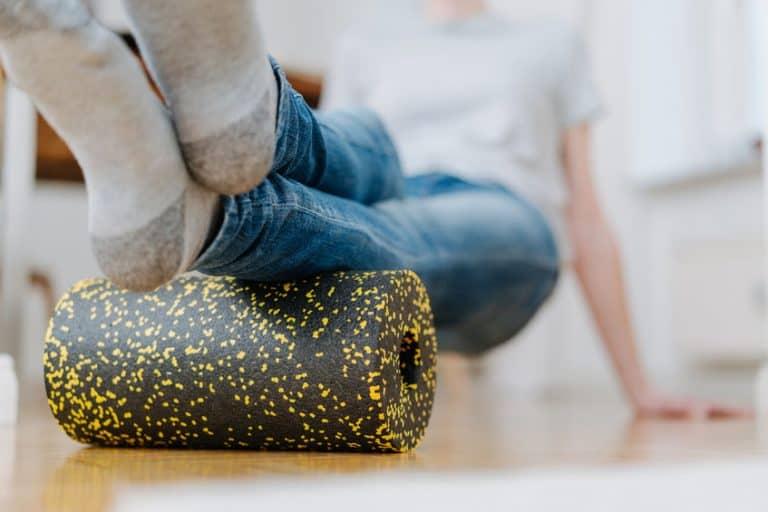 Pessoa com pés apoiados em rolo de espuma pequeno.