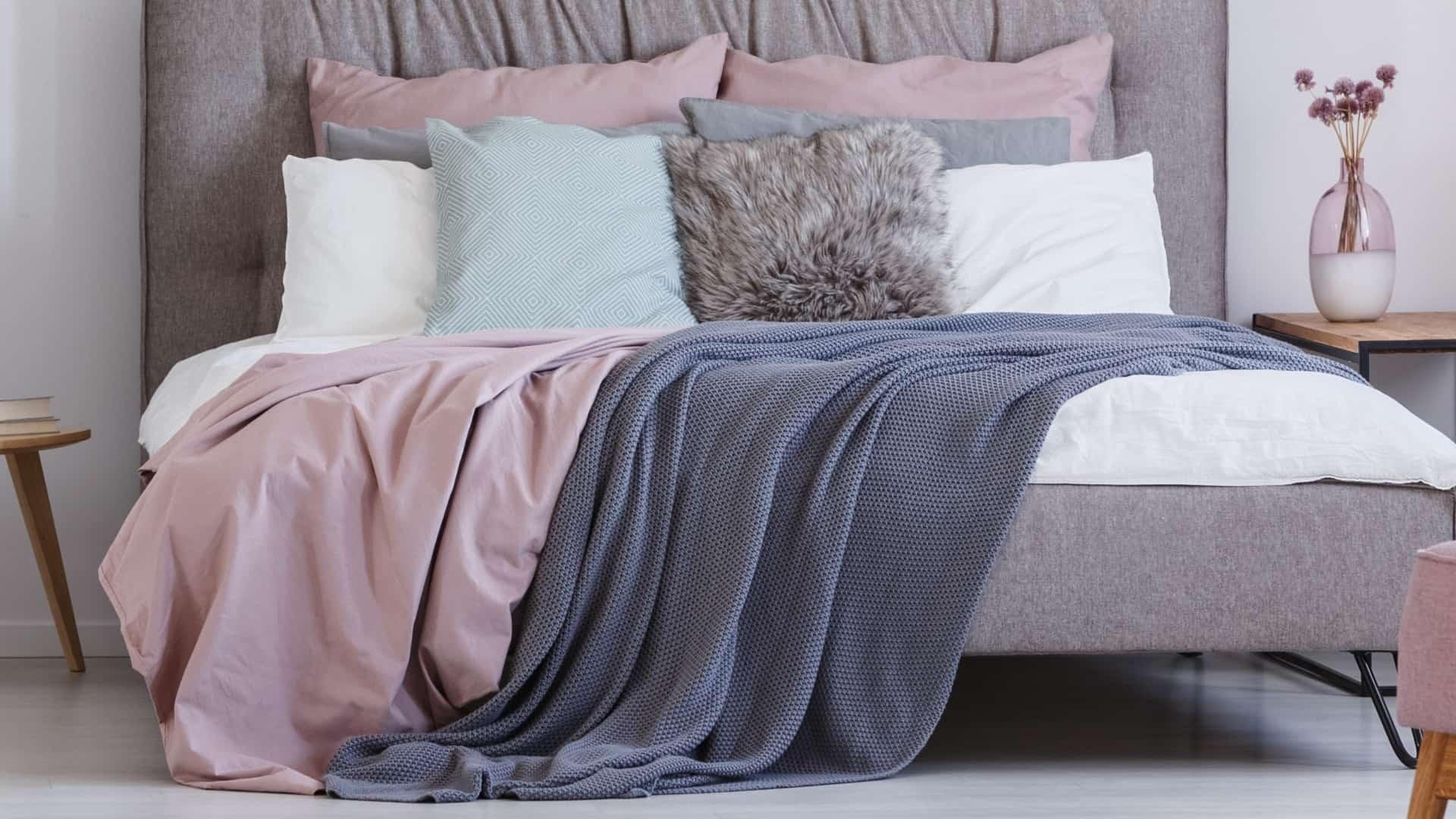 Imagem de cama com lençol, travesseiros e cobertas.