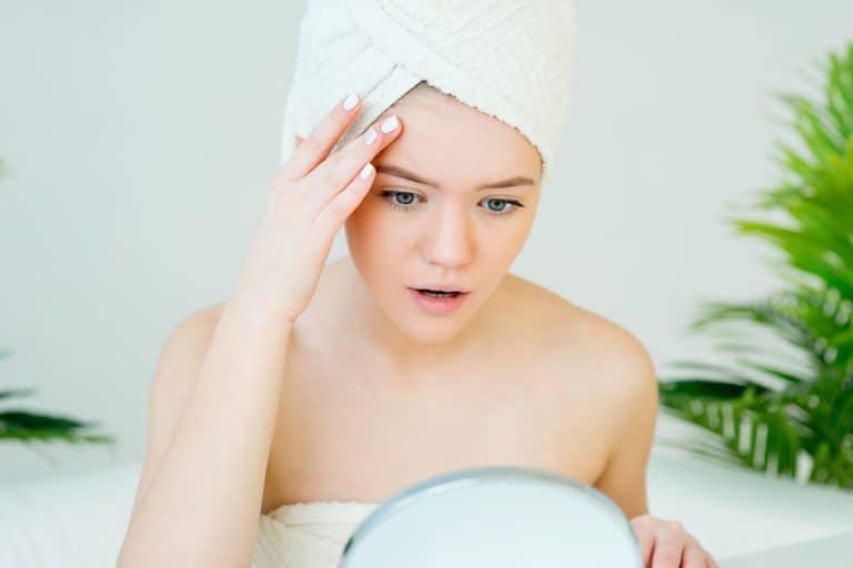 Imagem de mulher se olhando no espelho com toalha de banho.