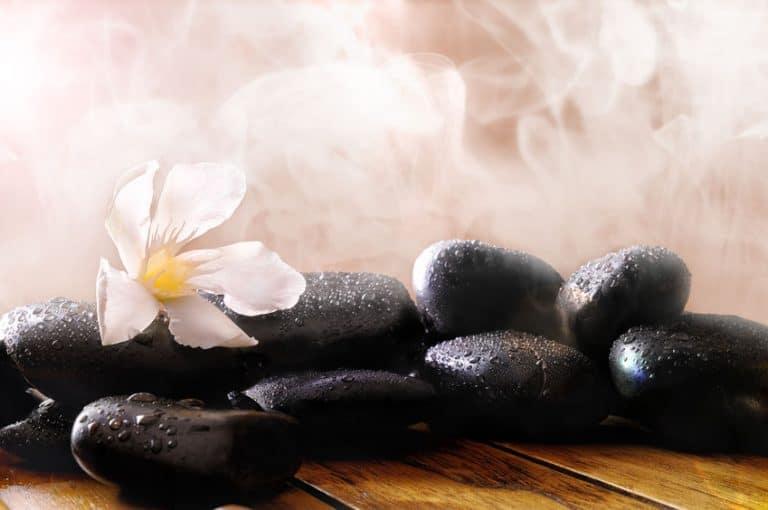 Imagem de pedras, flores e vapor em sauna.