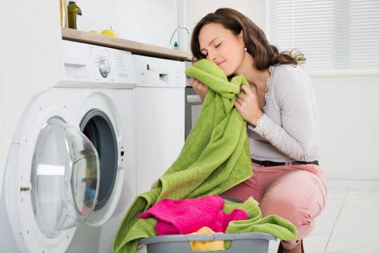 Mulher tirando roupas da secadora.
