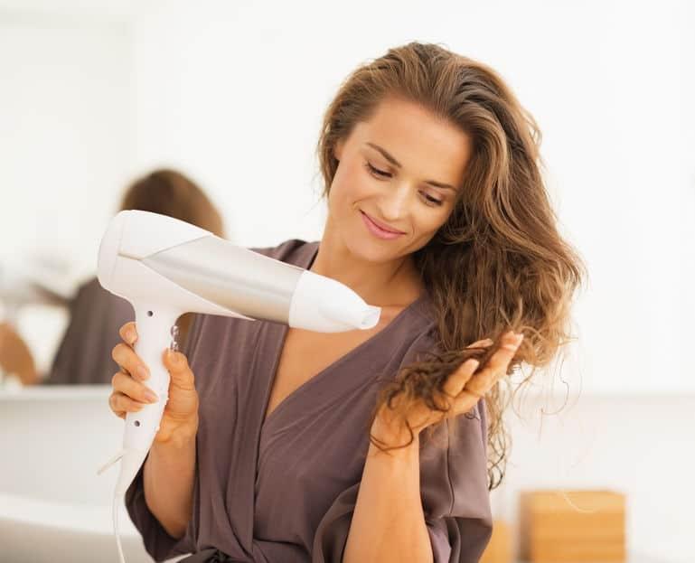 Mulher morena secando seu cabelo.