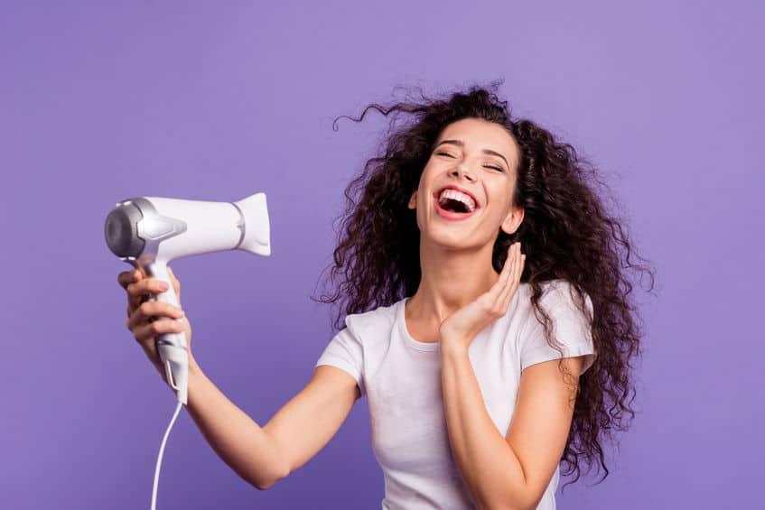 Mulher com cabelo enrolado secando cabelo.