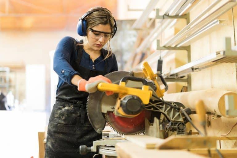Imagem de mulher trabalhando com serra circular de mesa.