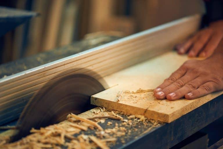 Imagem pessoa serrando madeira.