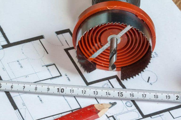 Imagem de serra de copo sobre projeto com régua e lápis.