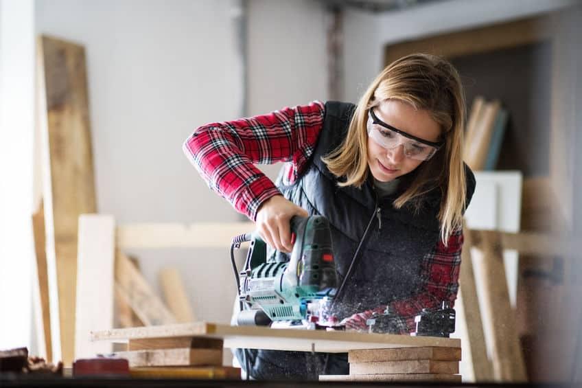 Imagem de mulher trabalhando com serra, cortando madeira.