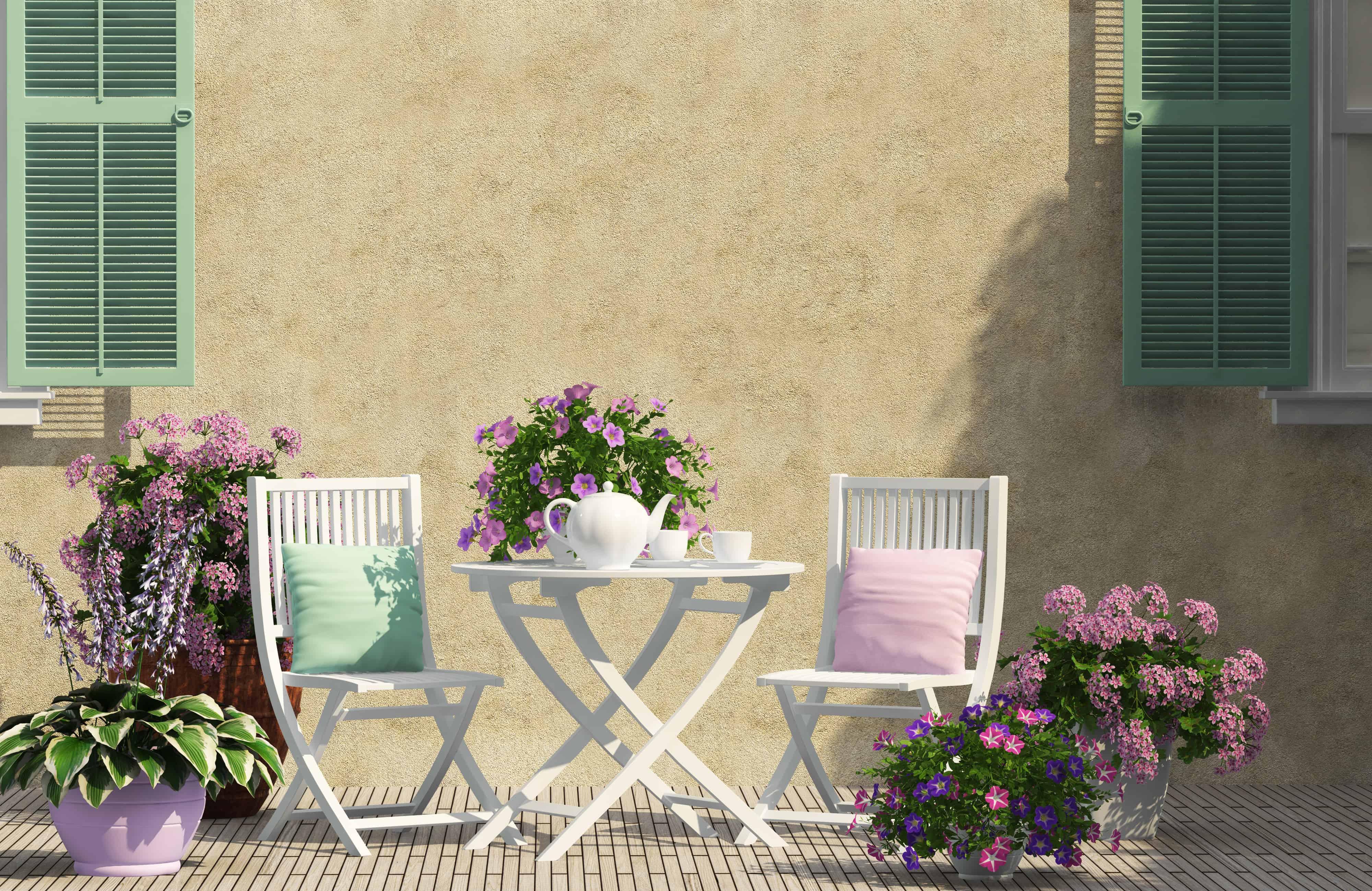 Imagem de mesa e cadeiras de jardim brancas.