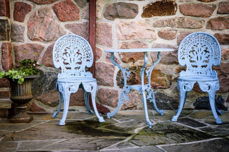 Imagem de mesa e cadeiras brancas de metal em jardim.