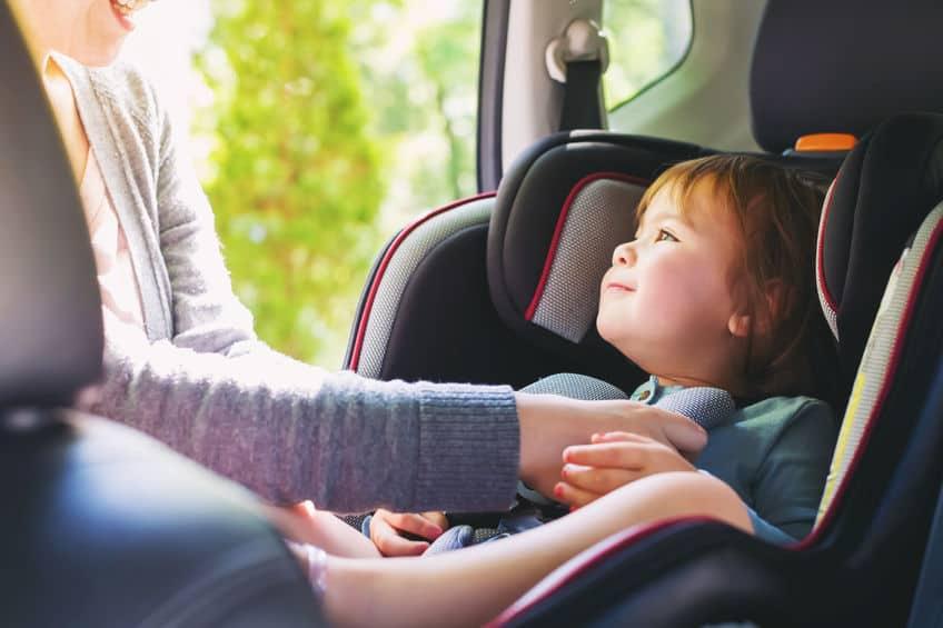Mulher acomoda bebê em uma cadeirinha de bebê para carro