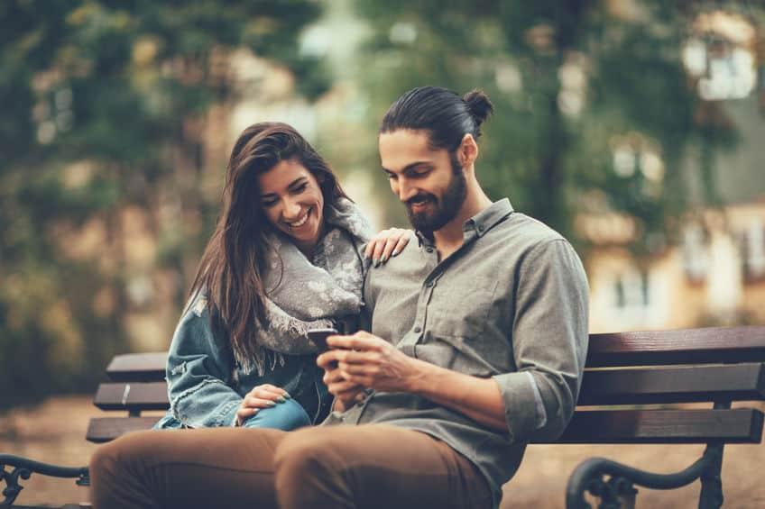 Imagem de casal em banco de praça mexendo em smartphone.