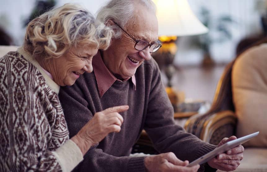 Imagem de casal de idosos mexendo no celular.