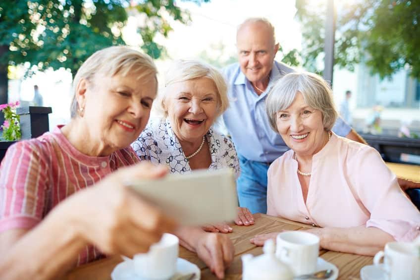 Imagem de grupo de idosos fazendo selfie.
