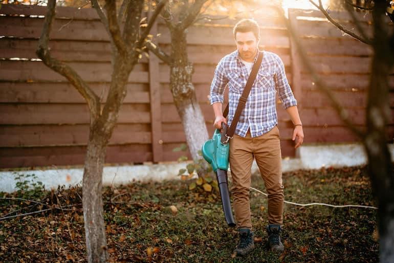 Homem em jardim com soprador de folhas.