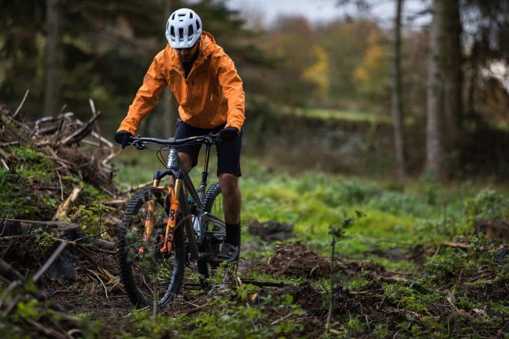 Imagem de homem andando de bicicleta em meio a floresta.