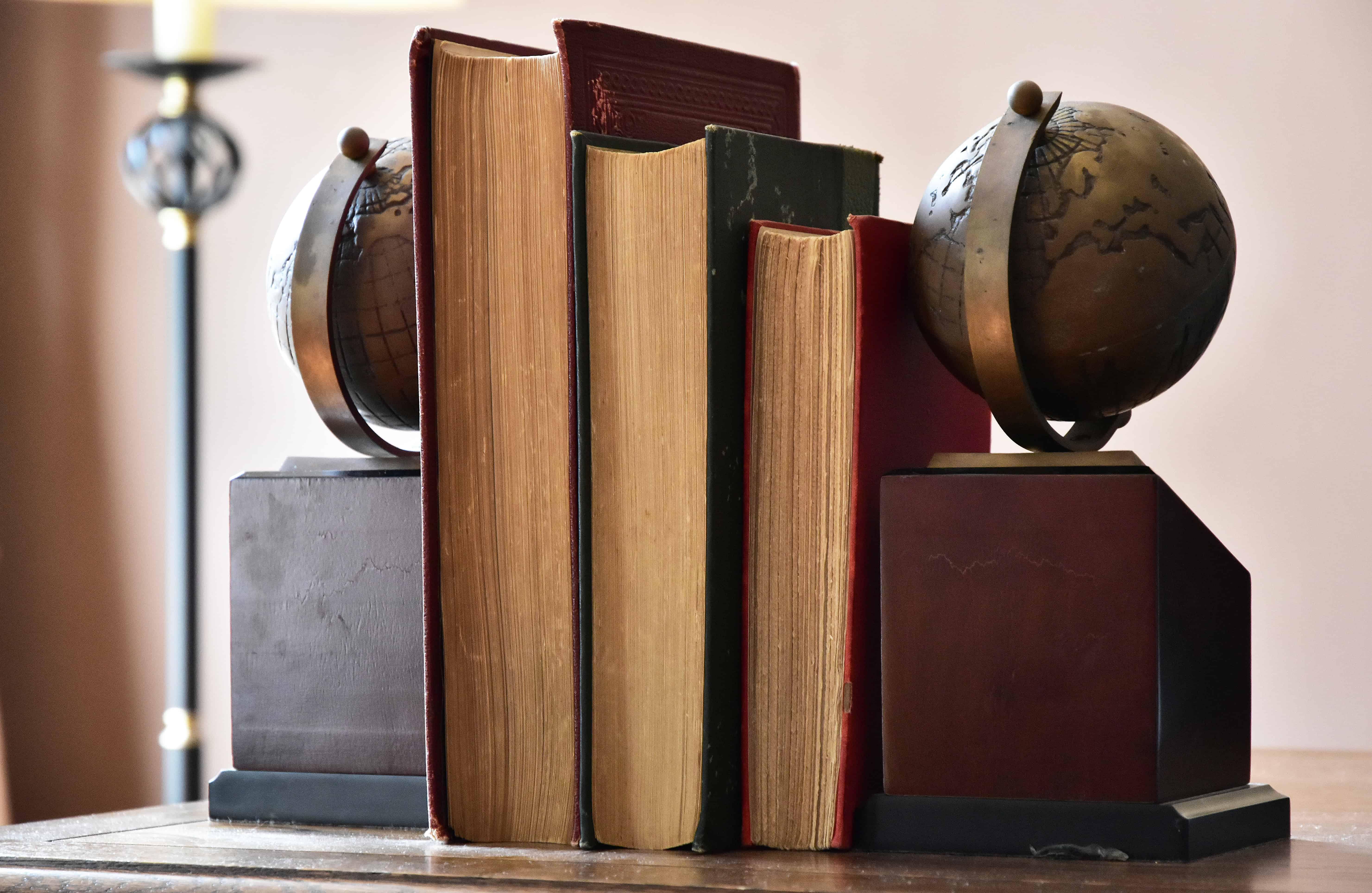 Imagem de livros com aparador de globo terrestre.