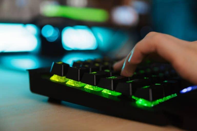 Imagem de teclado gamer com luz verde.