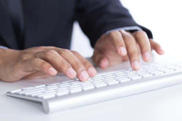 Digitando em teclado prata e branco.