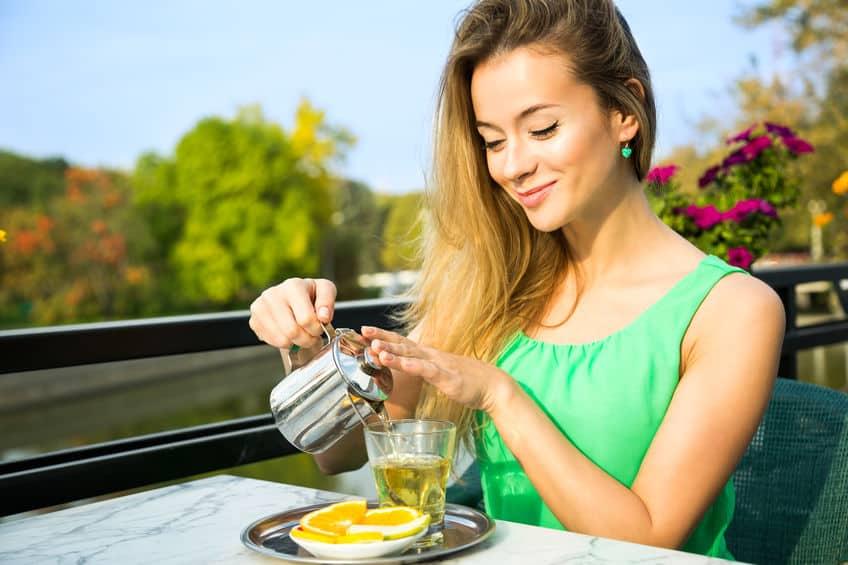 Uma mulher serve-se de chá utilizando um bule de metal