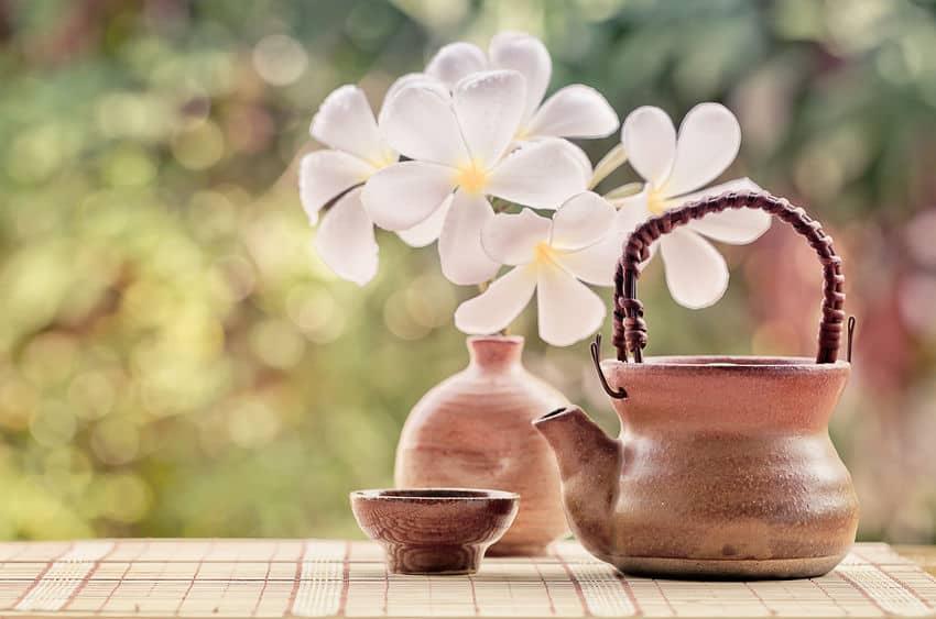 Em uma mesa estão um bule estilo vintage, uma xícara ou taça de xá e um vaso com flores brancas