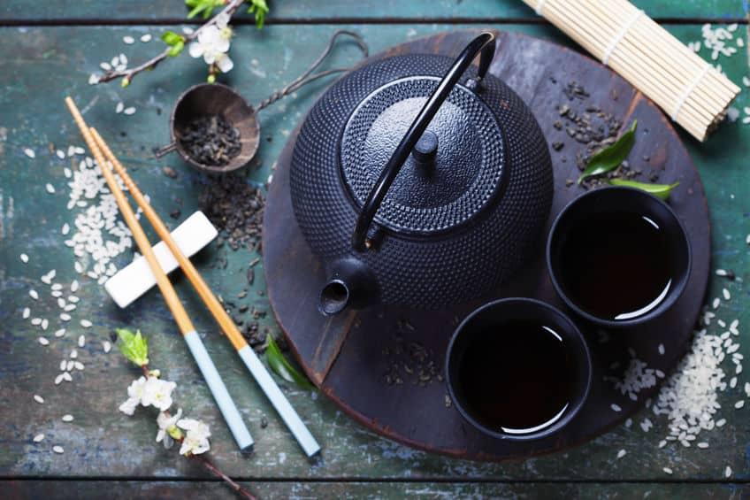 Imagem mostra um bule de ferro com duas xícaras em uma mesa ornada com utensílios da culinária oriental