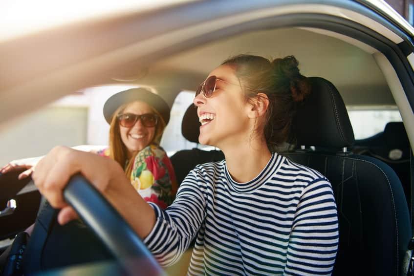 Imagem de mulheres dentro de carro.