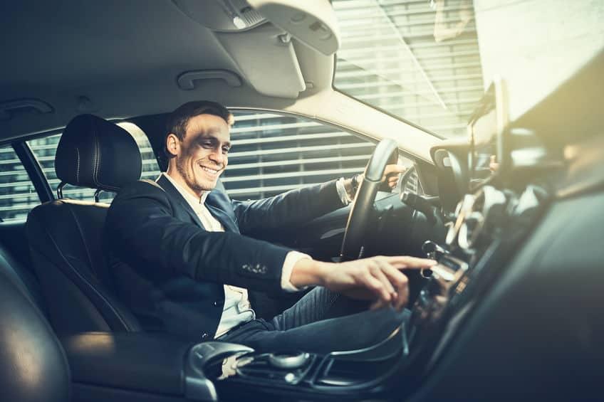 Homem ligando rádio dentro de carro.