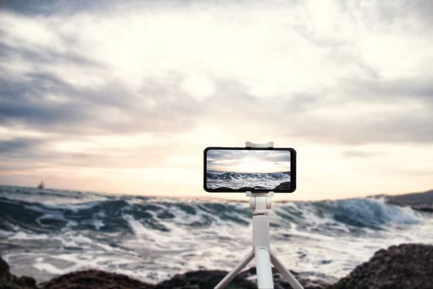 Fazendo fotos do mar com celular em tripé.