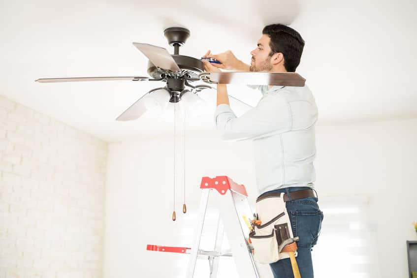 Homem instalando ventilador de teto em cima de uma escada