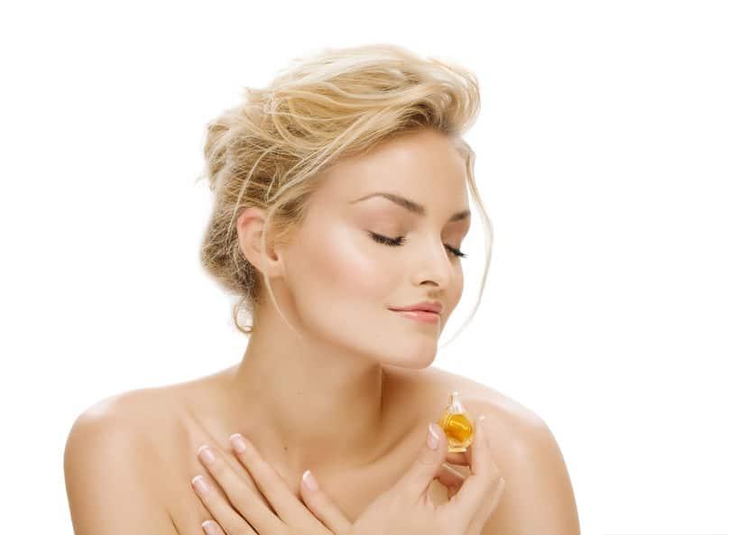 Mulher cheirando um perfume