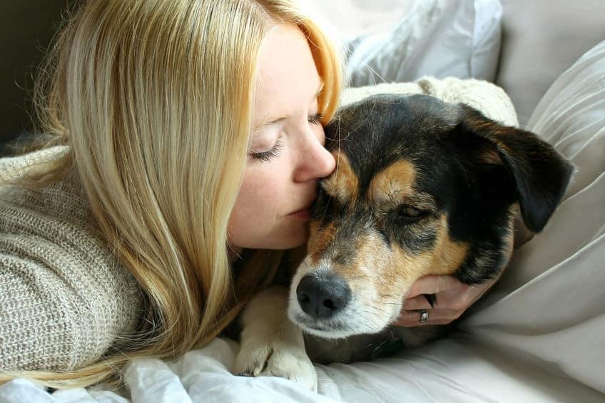 Imagem de dona dando beijo em seu cachorro.